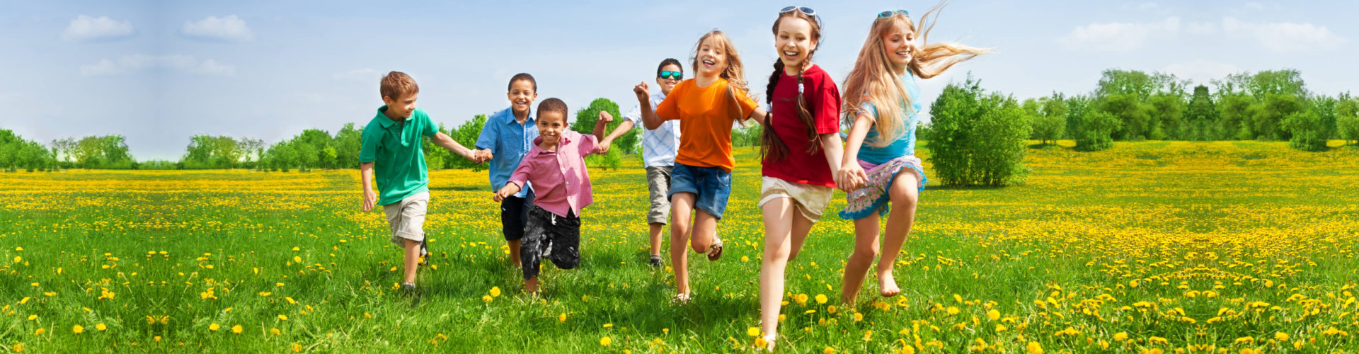 Large group of kids running in the dandelion spring field
