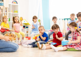 Group of kindergarten children play with musical toys